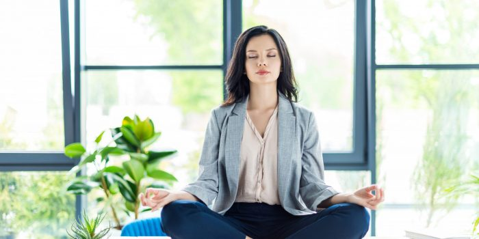 relaxed businesswoman with eyes closed meditating at workplace in office